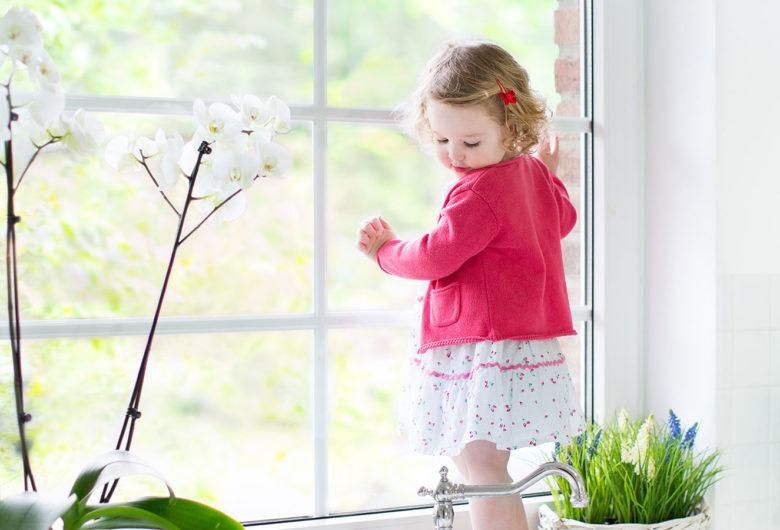 Enfant debout contre la fenêtre
