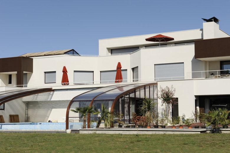 Photo représentant une maison en période estivale, volets fermés.